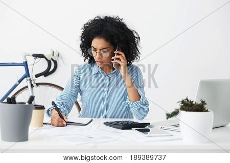 Attractive Young Dark-skinned Businesswoman With Afro Hairstyle Talking On Cell Phone And Writing So