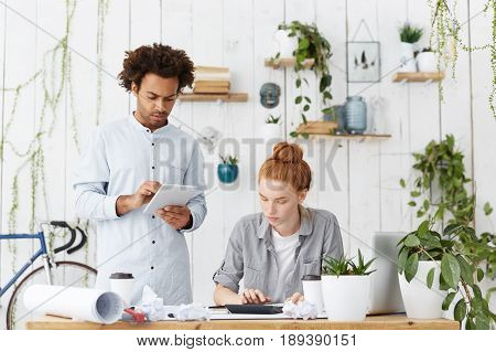 Team Work Of Hard-working Architect Workers. Attractive Male With Trendy Hairdo Holding Tablet And P