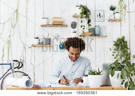 Afro American Dark-skinned Design Worker Sitting At Workplace Making Drawings Holding Smartphone Bei