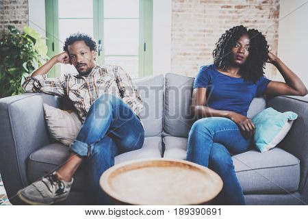 Young displeased black couple.American african men arguing with his stylish girlfriend, who is sitting on sofa on couch next to him with legs crossed.Man looking away offended expression on her face