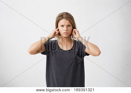 Unhappy stressed out teenage girl with tattoos on arms plugging ears with fingers doesn't want to hear annoying noise or ignoring stressful and unpleasant situation or conflict. Body language