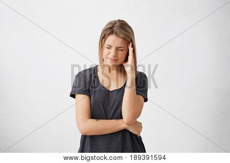 Negative Human Emotions And Feelings. Indoor Studio Shot Of Unhappy Young Woman Suffering From Bad H