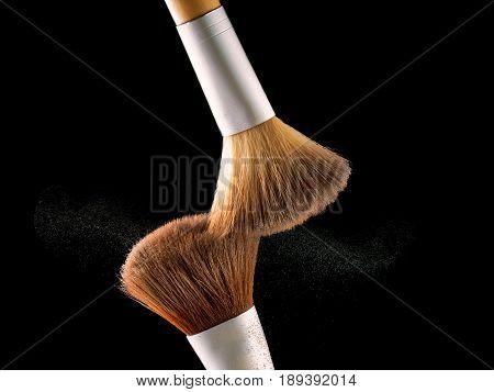 Cosmetic makeup brushes on black background flash explosion splash powder shadow blush