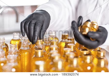 Selective Focus Of Factory Worker's Hands In Black Gloves Closing Bottles In Front Of Him With Screw