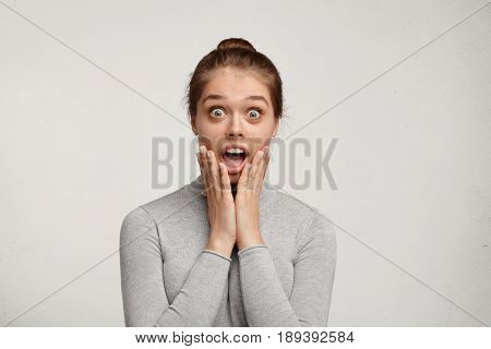 Horrified Caucasian Pretty Girl With Green Big Eyes Posing In Studio With Opened Mouth Holding Hands