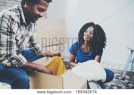 Side view of young black american african couple with moving boxes in new apartment.Cheerful couple sitting in empty new house.Horizontal, blurred background