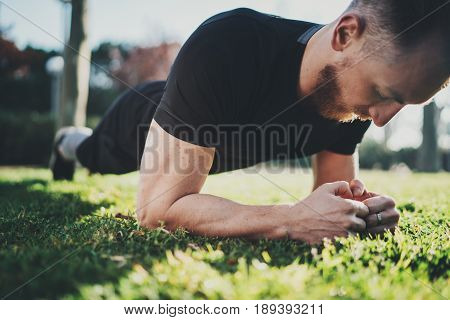Outdoor Workout lifestyle concept.Young Muscular athlete man doing abdominal exercises before training.Muscular athlete exercising outside in sunny park. Blurred background.Horizontal