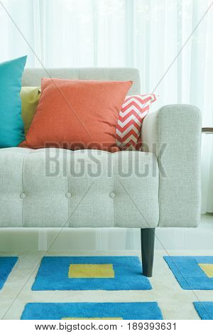 Orange And Green Pillows On Sofa With Graphic Pattern Carpet