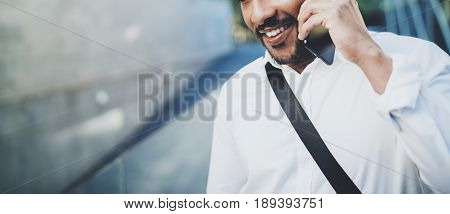 Portrait of happy American African man using smartphone to call friends at sunny street.Concept of happy young people enjoying gadgets outdoors.Blurred background.Horizontal wide, cropped