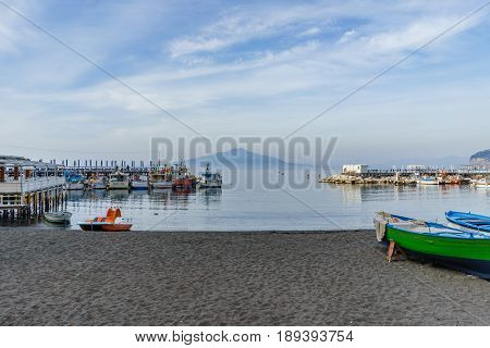 Sorrento Italy - April 1 2017: The fisherman boats in beautiful sea in south Italian coastal village with the Vesuvio volcano in the background Spring.