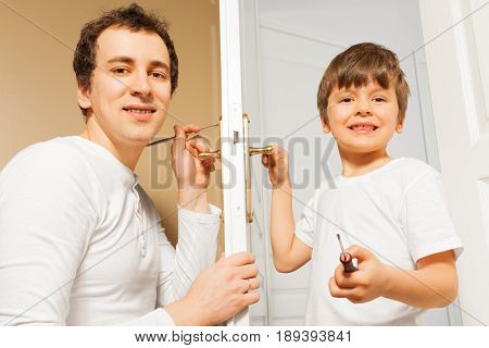 Portrait of happy father teaching his six years old son to fix door-handle at home