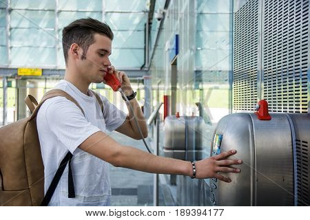 Young attractive man speaking on public phone in train station or airport