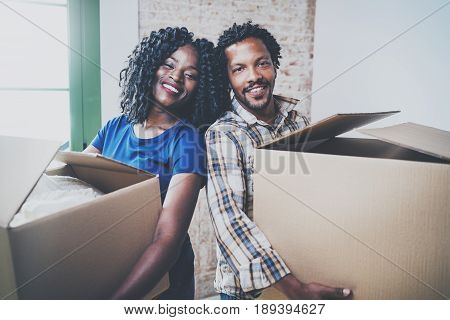Happy young black african man and his girlfriend moving boxes into new house together and making a successful life.Cheerful family standing in empty new apartment.Horizontal.Blurred background