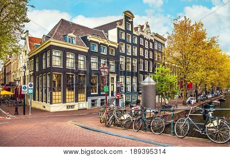 Urban landscape in Amsterdam Netherlands. Panorama street with bicycle tree and road traditional Dutch architecture.