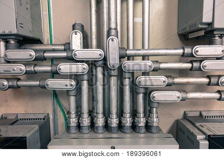Electrical Conduit connected to junction box for connect electrical cable in box with vintage tone for industrial technology concept.