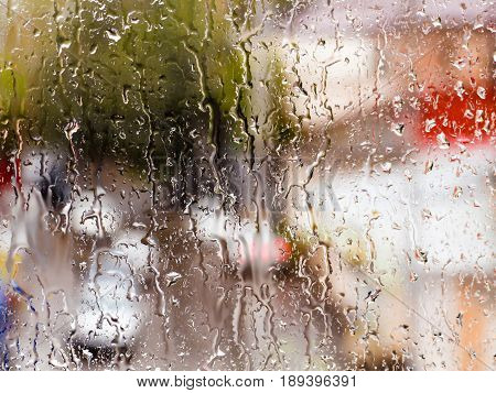 Rain drops on glass window. The cityscape outside the window in a blur. The bokeh effect.
