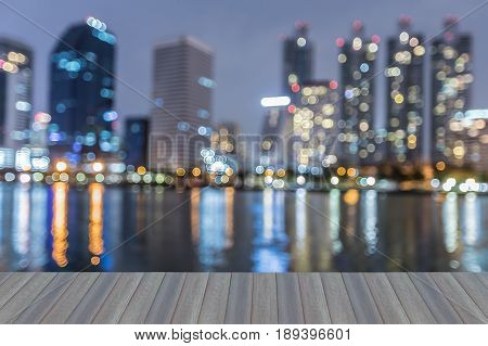 Opening wooden floor Night blurred bokeh office building with reflection over water abstract background