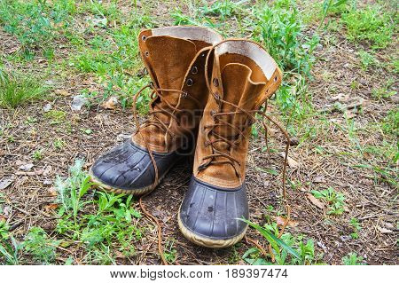 Pair of wet hunting boots on glade in forest at sun autumn day
