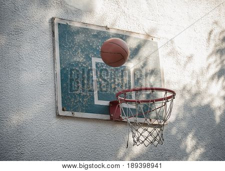 Ball Basketball Going Through Rustic Old Hoop With Backboard