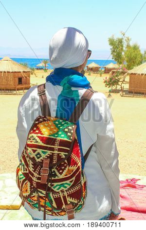 Young Lady Standing By The Cottage In A Camp In Sinai, Taba Desert With The Background Of The Sea An