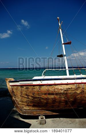 Abandoned fishing wooden rowboat at seaside at sunny summer day.