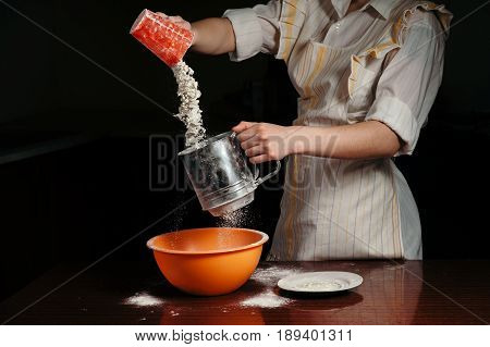 Female hands are pouring flour into a steel sifter. Flour scatters in the air.
