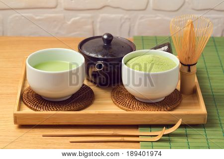 Matcha green organic tea cup and powder on wooden table