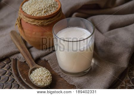 Vegan sesame milk in glass and white sesame seeds in a clay pot on a wooden table. Raw food diet. Horizontal photo without people.