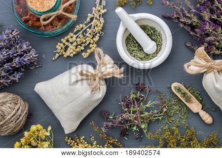Medicinal Herbs, Mortar Of Healing Herbs, Sachet And Bottle Of Healthy Drugs On Wooden Table. Herbal