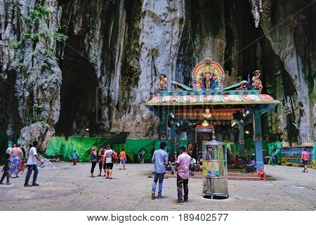 Batu Caves, Malaysia - February 7, 2016: Tourists visit to the the most popular Hindu shrines Batu Caves. The interior with Indian Deity Statues under the arches of the cave