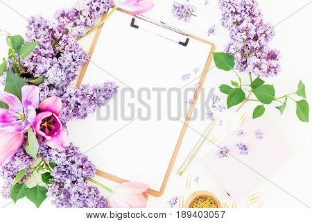 Freelancer or blogger workspace with clipboard, notebook, lilac and tulips on white background. Flat lay, top view. Beauty blog workspace.