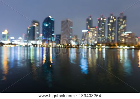Blurred city light office building with water reflection abstract background