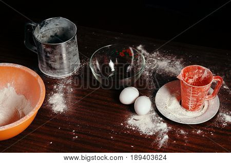 Orange cup measuring cup and a steel sieve two eggs stand on a wooden table on a black background. Flour.