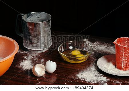 Scattered flour on a wooden table broken eggs in a glass bowl eggshell.