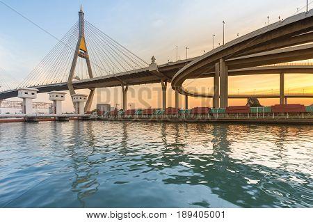 Sunset over suspension bridge connect highway river front Bangkok Thailand