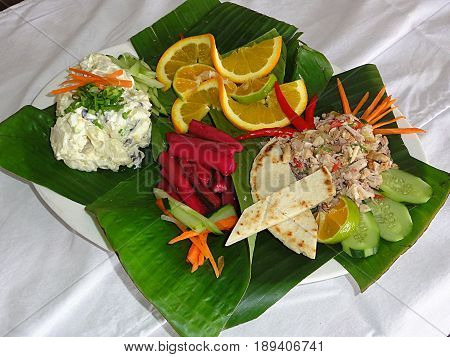 Chamorro cuisine- beef kelaguen and potato salad in banana leaves, top view Favorite foods of Chamorros, people from the Northern Mariana Islands. Beef kelaguen  (raw beef cooked only with a marinate) with peppers and cucumber, potato salad, pickled radis