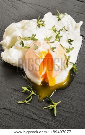 open organic poached egg with thyme on slate