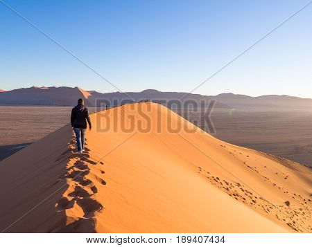 SOUSSUSVLEI NAMIBIA - JUNE 20 2016: People watching sunrise form the Dune 45 in the Sossusvlei area of the Namib Desert in Namibia.