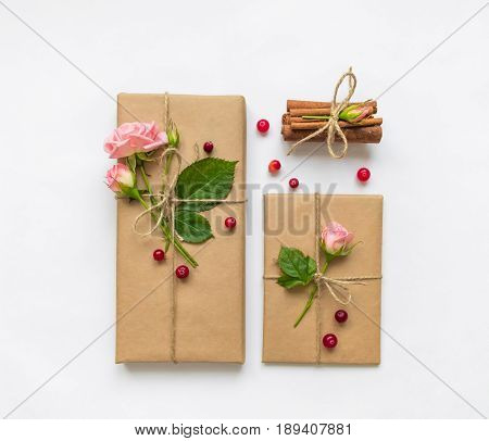 Vintage gift box and envelope in eco paper on white background. Presents decorated with cinnamon roses and berries. Valentine's day or other holiday concept top view flat lay overhead view