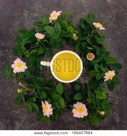 Summer bright composition of cup of herbal tea dogrose branches and flowers on dark marble table. Flat lay top view