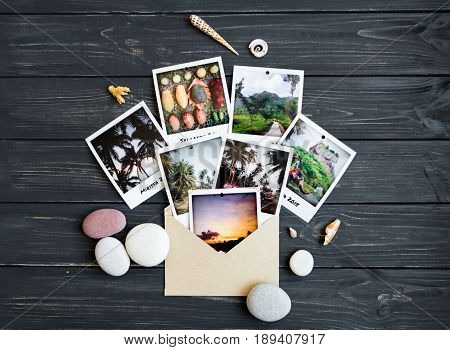 Holiday resort memories: photos stones seashells citrus fruits on black vintage wooden background. Travel photo tropic vacation memories. Flat lay top view