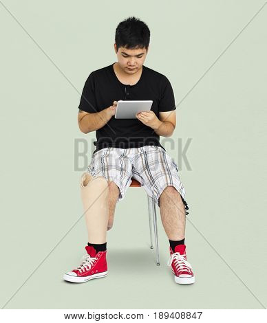 Disability Young Man with Prosthesis Leg Using Tablet Studio Portrait