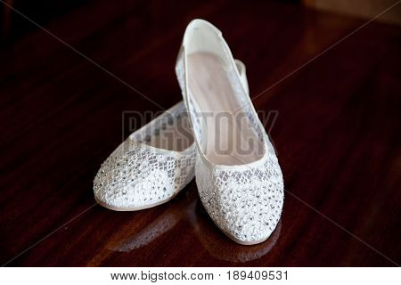 Summer ballet flats of white color against a dark background