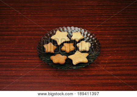 Ready home ginger biscuits in the form of stars on a plate. Alone.