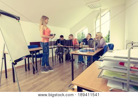 Woman young teacher near whiteboard teaching to bored college students in classroom