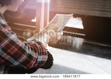 Summer travelhipster girl are looking for places to go on the map at platform of railway station. travel concept.