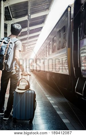 summer dayhipster boy traveler with luggage in the railway. vintage effected photo. Travel concept