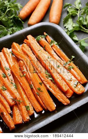Roasted vegetables. Cooked carrots with herbs in baking tray close up