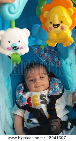two months old baby boy in pushchair with spinning toys