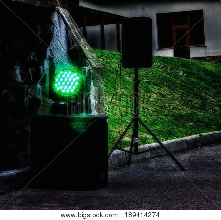 Searchlight for color music glows green in the open air near powerful music speakers